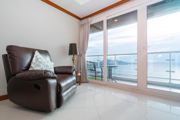 Кондо с видом на море с диваном у балкона