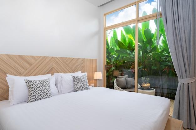 緑豊かな庭園と家のバルコニー付きのベッドルーム