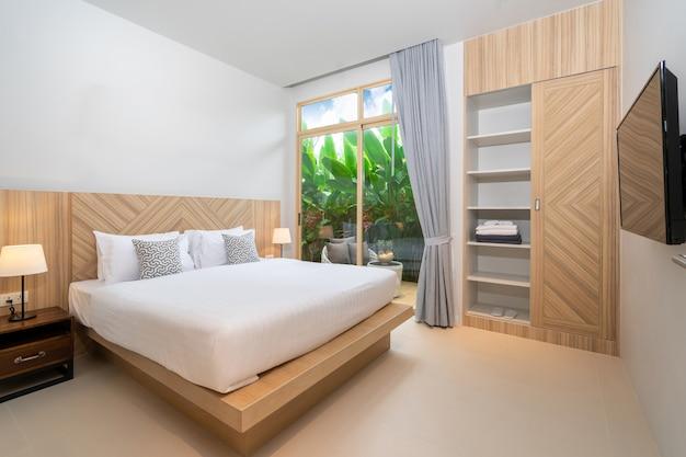 緑豊かな庭園と家のバルコニー付きのベッドルームのインテリアデザイン