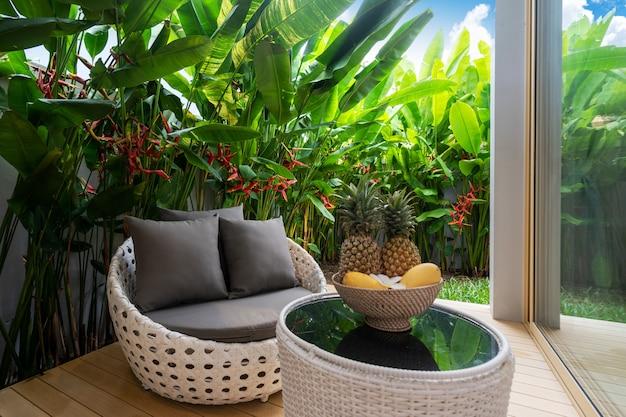 テーブルの上のフルーツ付きのバルコニーと緑豊かな庭園