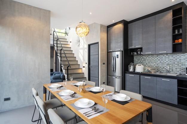 Обеденный стол на открытой кухне полностью оборудованная кухня
