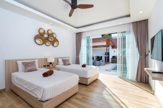 Двуспальная кровать в просторной спальне с потолочным вентилятором и выходом к бассейну