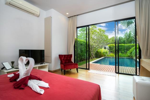 Современная спальня с выходом к бассейну и красным диваном