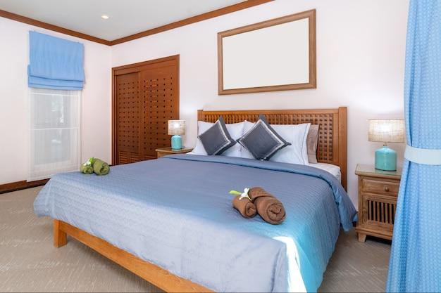 青いシーツと木製のワードローブを備えた広々としたベッドルーム