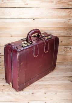 Древний багаж на фоне деревянного пола - дерево
