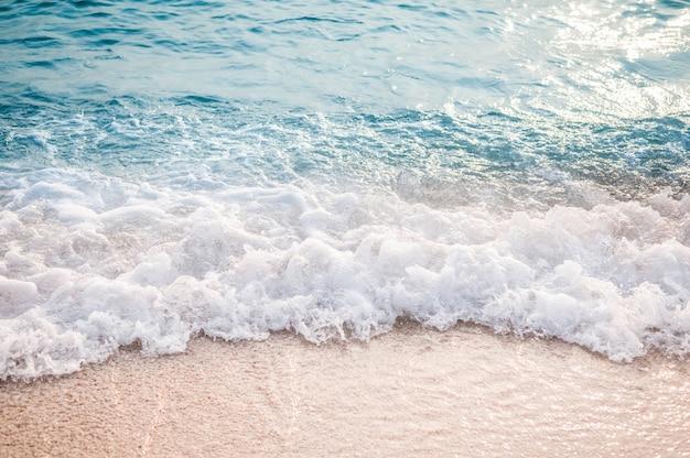 砂浜のビーチで青い海の波