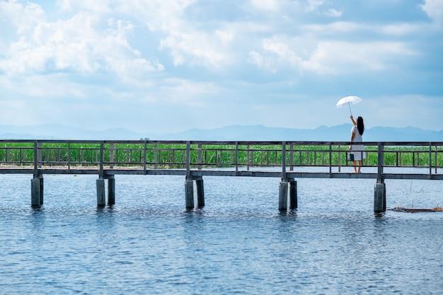 木製の橋の上を歩く一人の女性の白いスーツ