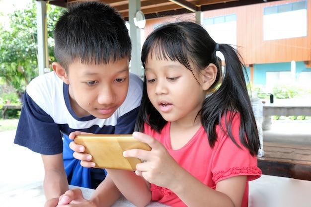 Девочка и мальчик любят играть на смартфоне