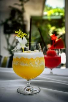 テーブルの上の夏の飲み物のパイナップルのスムージージュースのガラス