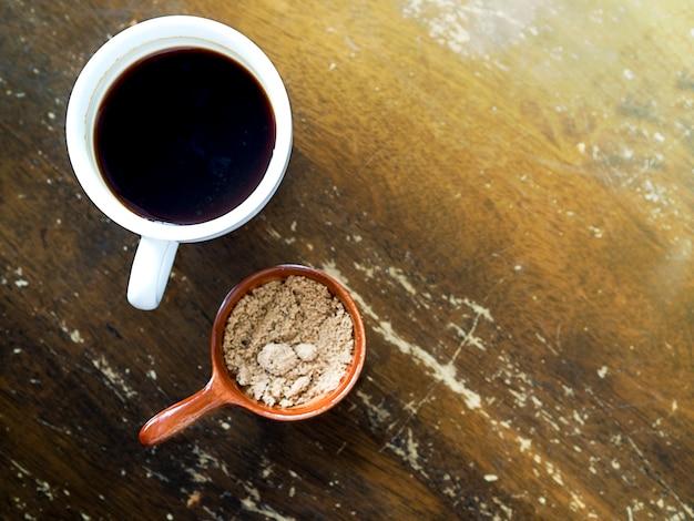 Черный кофе или американский кофе, подаваемый с бразильским сахаром на старинном деревянном столе