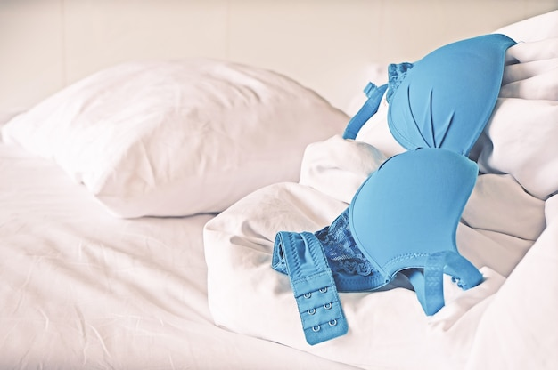 未完成のベッドで女性の黒いブラジャーのトップビュー。ヴィンテージトーン効果。バレンタインコンセプト