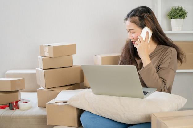 Счастливый азиатский молодой предприниматель, разговаривая по смартфону с клиентом для заказа тэкс, она улыбнулась для успеха продаж в домашнем офисе