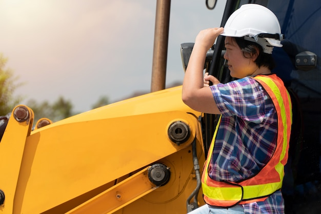 Женщина инжиниринг в белом защитном шлеме стоит перед экскаватором