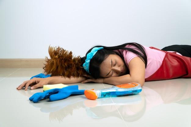 アジアの主婦は、家事の疲れのために床に横たわっています。さまざまな洗浄装置を周囲に配置して