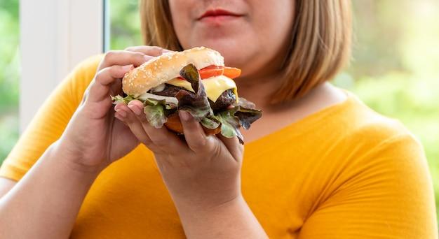 ハンバーガーを保持している空腹太りすぎの若いアジアの女性、彼女のすべての時間と食べ過ぎ、大食と過食。