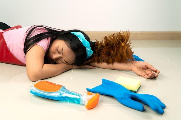 アジアの主婦は、家事の疲れのために床に横たわっています。