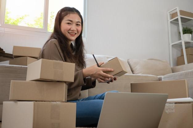 Счастливые молодые азиатские предприниматели расставляют коробки для доставки продуктов покупателям.