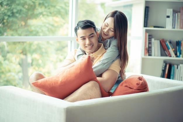 Счастливая пара, сидя на диване и быть женщиной, обнимая своего парня с любовью в гостиной