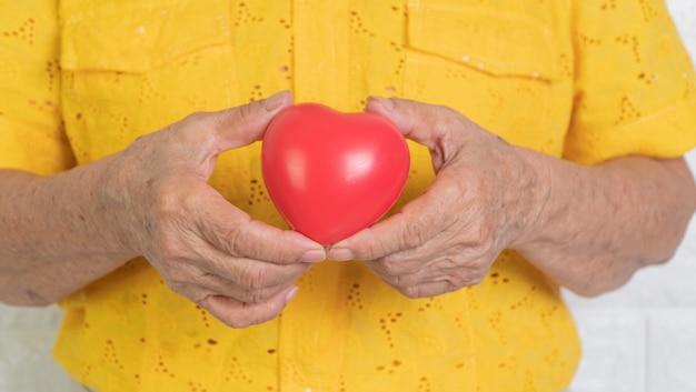 赤いハートを保持している高齢者のアジアの女性。孤独の概念と子供と近いものによって世話される必要がある