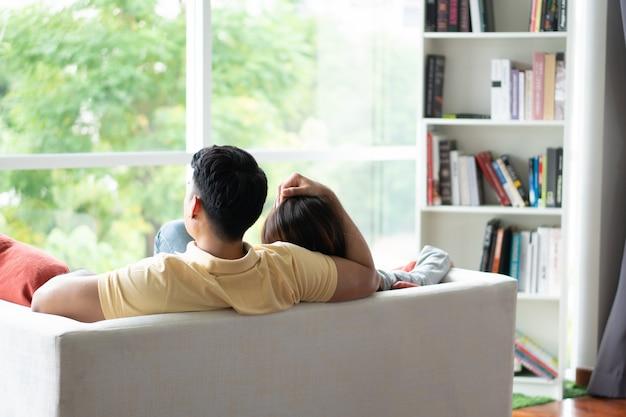 ソファーに座って、リビングルームで愛をこめて彼のガールフレンドを抱きしめる男性となる幸せなカップル。