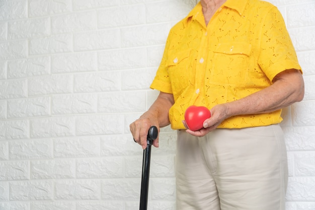 Пожилая азиатская женщина держа штат и красное сердце.