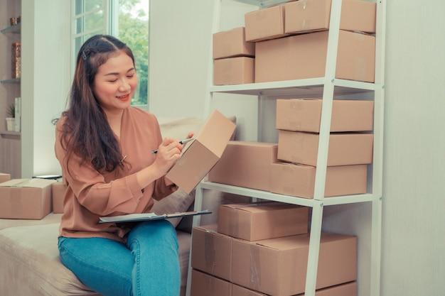 Молодой предприниматель, сидя на диване, писать на коробке