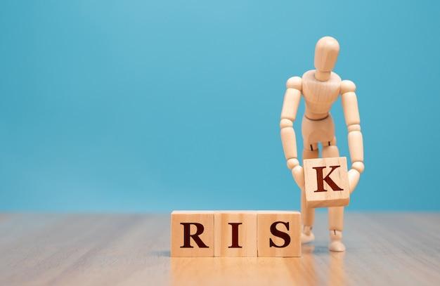 Деревянная марионетка стоя и держа деревянный куб с словом риска.