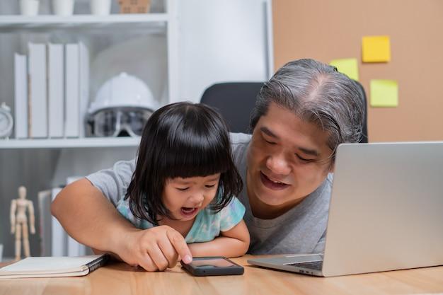 アジアの父親は娘と一緒に家で働いており、学校でのオンライン学習を一緒に勉強しています。