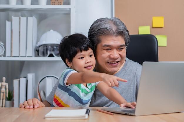 アジアの父は娘と一緒に家で働いています。