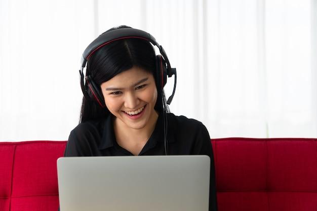 ラップトップでビジネスパートナーとソファとビデオ会議に座って幸せなアジア女