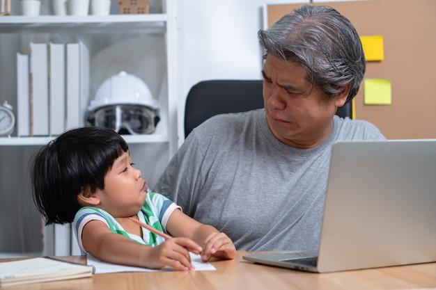 混乱に陥った娘と一緒にラップトップでホームオフィスで働くことを試みるアジアの父親