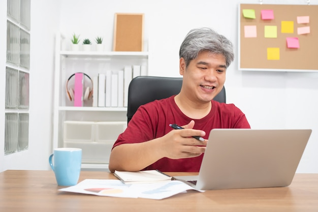 Видеоконференция азиатского бизнесмена вызывая на беседе портативного компьютера веб-камера для онлайн учебного курса обучения дома.