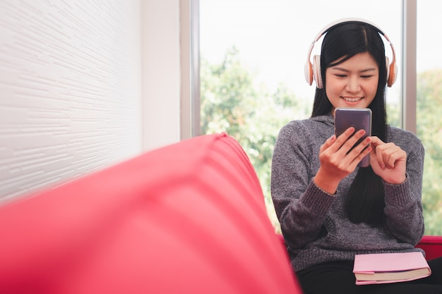 かわいいアジアの女性は午前中にソファーに座っているし、携帯電話でメッセージを送信します