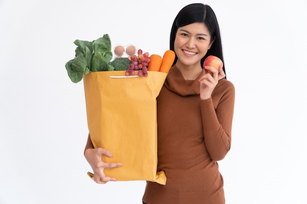 Счастливая азиатская женщина усмехается держит яблоко и носит бумажный пакет покупок
