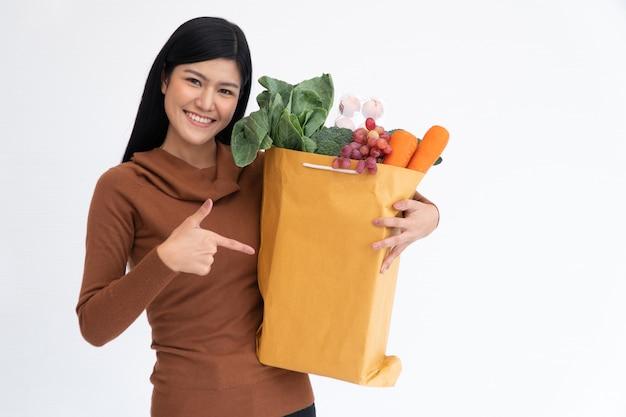 Счастливая азиатская женщина усмехаясь и указывает палец к бумажному пакету и носит хозяйственную сумку