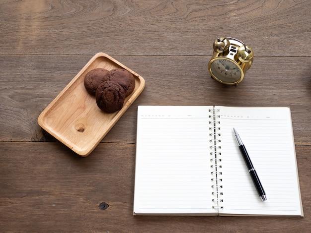 クッキーの開いた空のノートブック側と木製のテーブルに金色の時計があります
