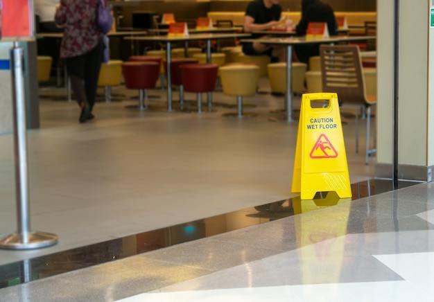 Желтый пластиковый конус со знаком с предупреждением о влажном полу в ресторане в универмаге