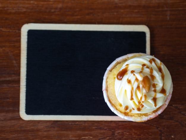 バニラカップケーキと黒板のトップビュー