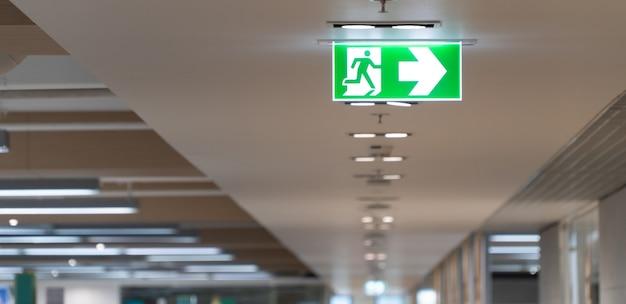 Зеленый знак пожарной лестницы висит на потолке в офисе.