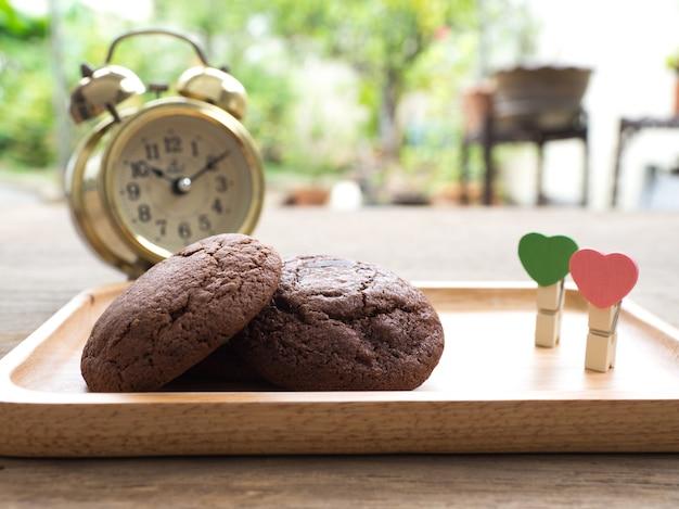 Домашнее мягкое темное шоколадное печенье, помещенное на деревянную тарелку с скрепкой в форме сердца