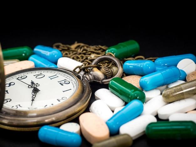 Антикварные часы с разноцветными лекарственными средствами и капсулой находятся на черном фоне