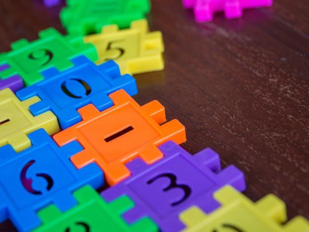 カラフルなパズル木製のテーブルにジグソーパズルのプラスチックナンバー。教育と数学の学習の概念