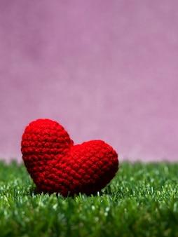 緑の芝生の背景に手作りの赤い糸の心