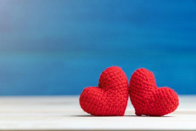 Рука делает две пряжи красное сердце на деревянный стол и синий фон