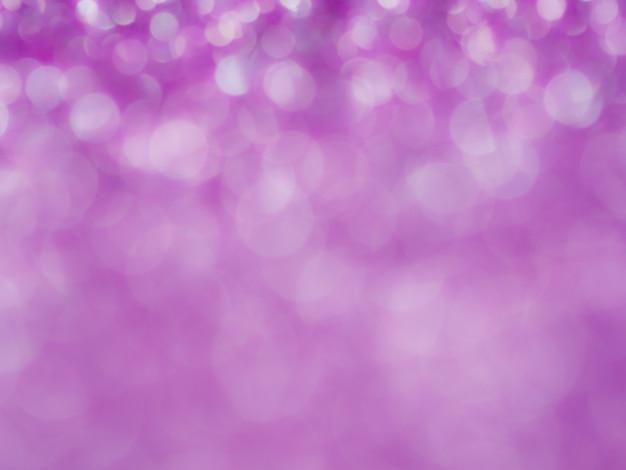 ボケ味を持つバイオレットの抽象的なキラキラ背景。ぼやけて柔らかいピンク