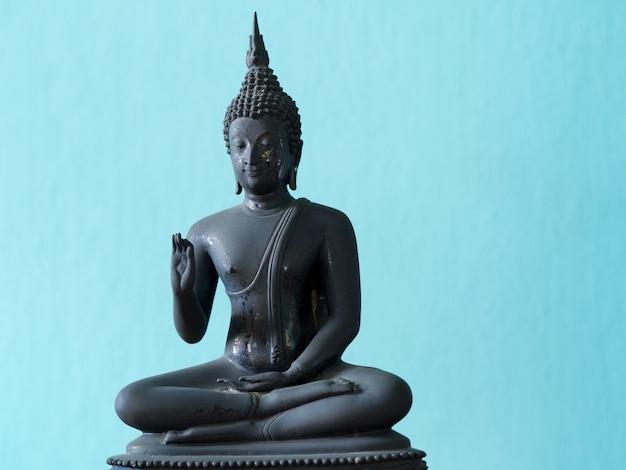 Античная статуя будды на деревянном столе.