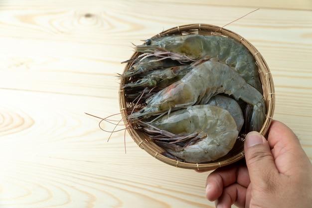 男性の手は竹ボウルに新鮮な生太平洋白エビのグループを保持しています
