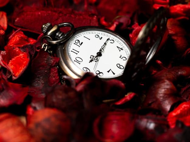 Золотые винтажные карманные часы на деревянном столе с красными сухоцветами с ароматом
