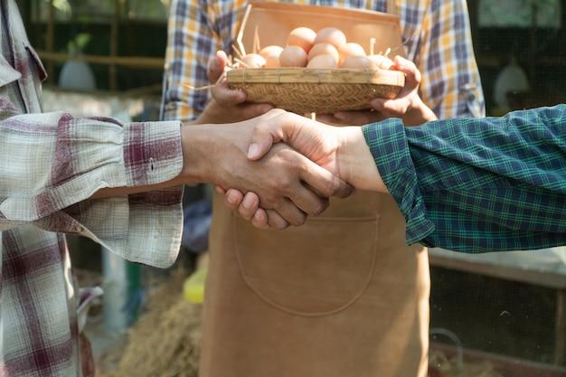 Бизнесмены пожимают друг другу рукопожатие, заключив сделку с фермером.