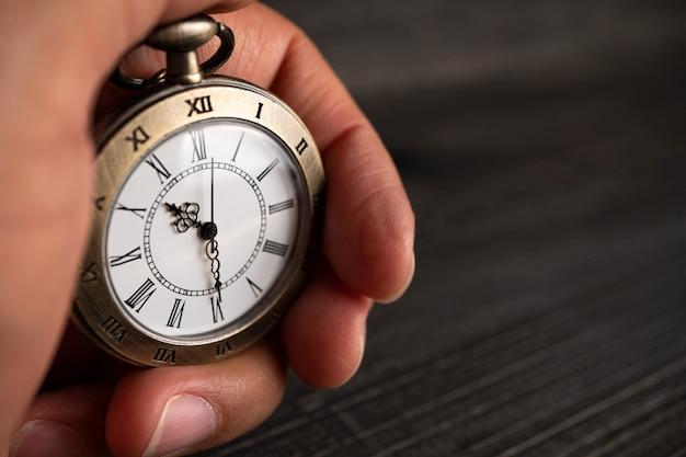 男性の手は懐中時計を握る